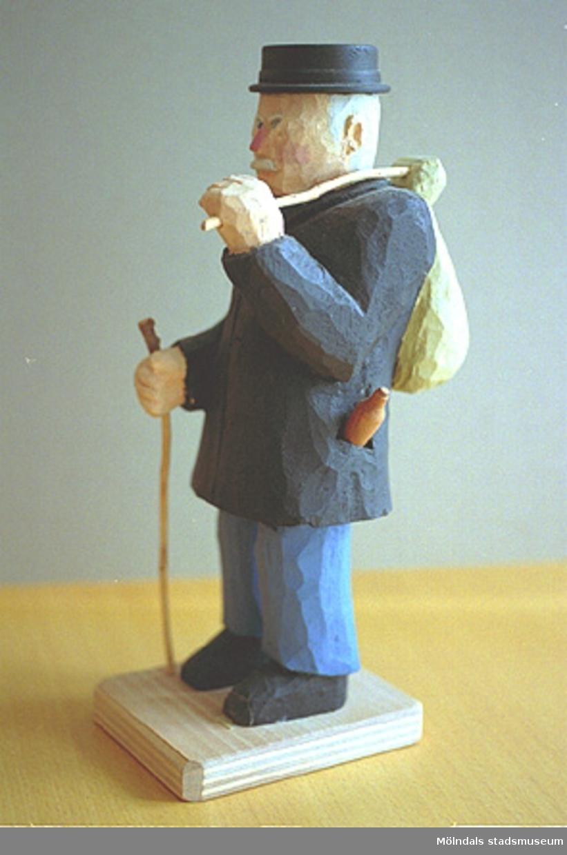 """En hattförsedd man som har en påse på ryggen. Han håller en käpp i ena handen. I fickan skymtar man en ölflaska. Harry Bergmans """"gubbar"""" (träfigurer)."""
