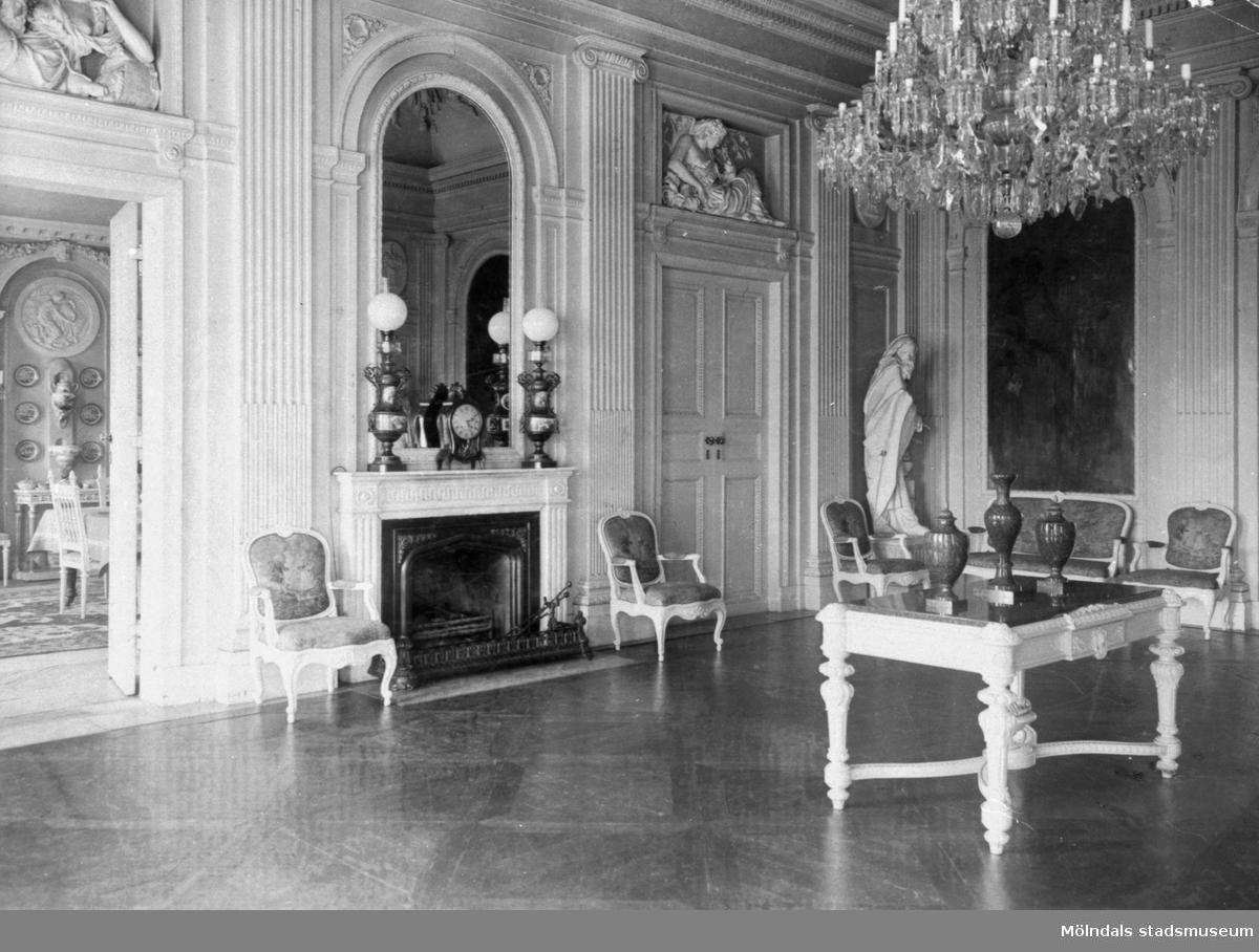"""Stora salongen på Gunnebo slott. I förgrunden står ett bord med tre urnor på. I bakgrunden till vänster finns en öppen spis samt några stolar. Till höger om spisen, ovanför dubbeldörren sitter dörröverstycket """"Trädgårdsodling"""" och i bildens mitt står statyn """"Vintern"""" av Gioacchino Frulli (1766-1801)."""