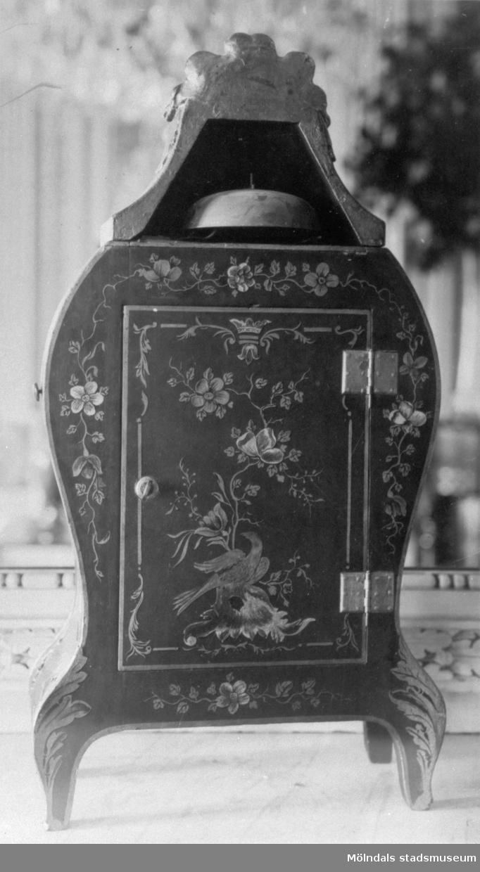Bordsklocka tillverkad av urmakaren Petter Ernst (1714-1784), Stockholm, omkring 1775. Baksida av grönt lack med dekor i guld och färger, här med stängd lucka. För framsida se bild: 1995_0981. Gunnebo slott 1930-tal.