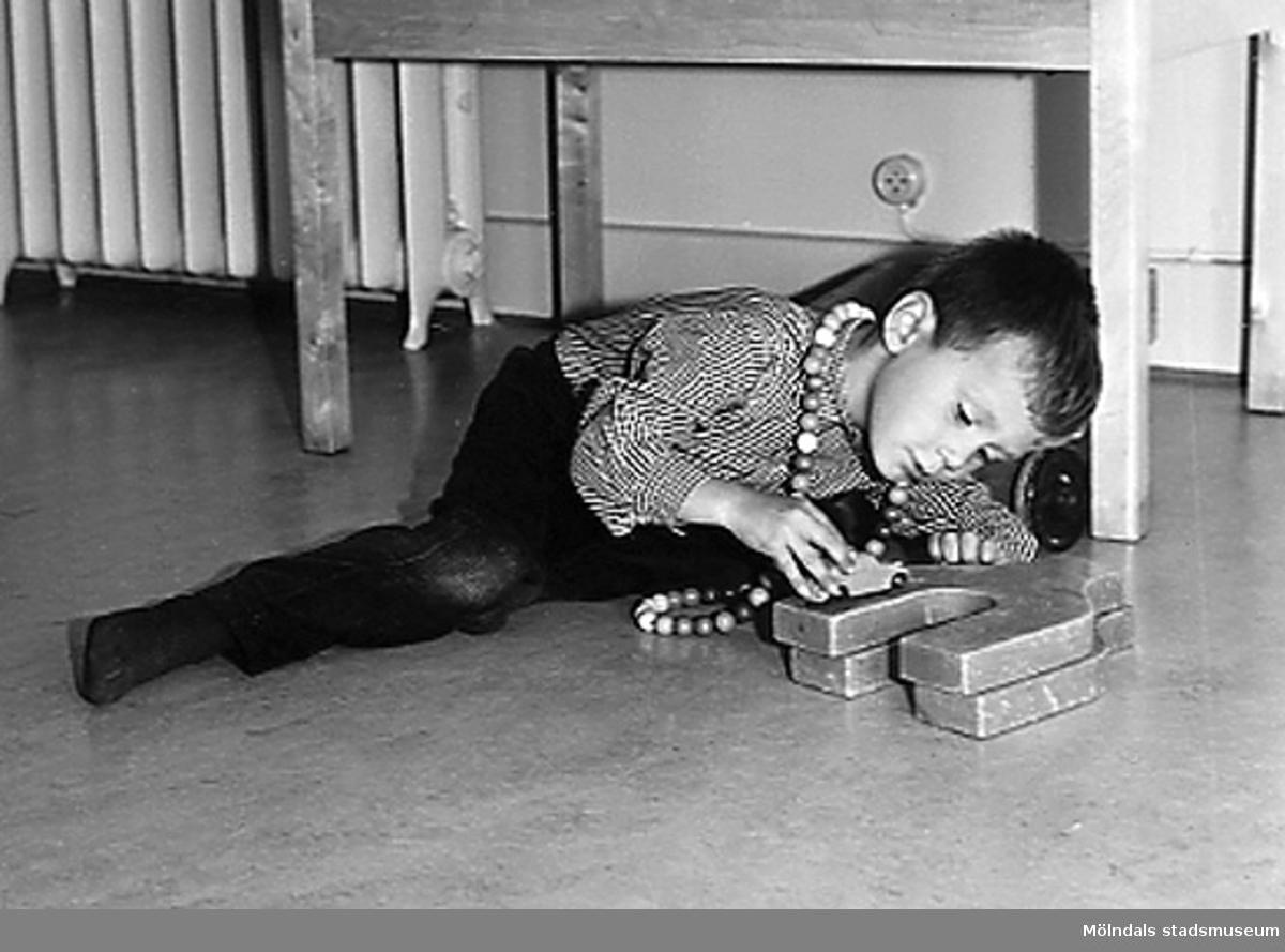 En pojke som leker på golvet med byggklossar vid Holtermanska daghemmet 1953.