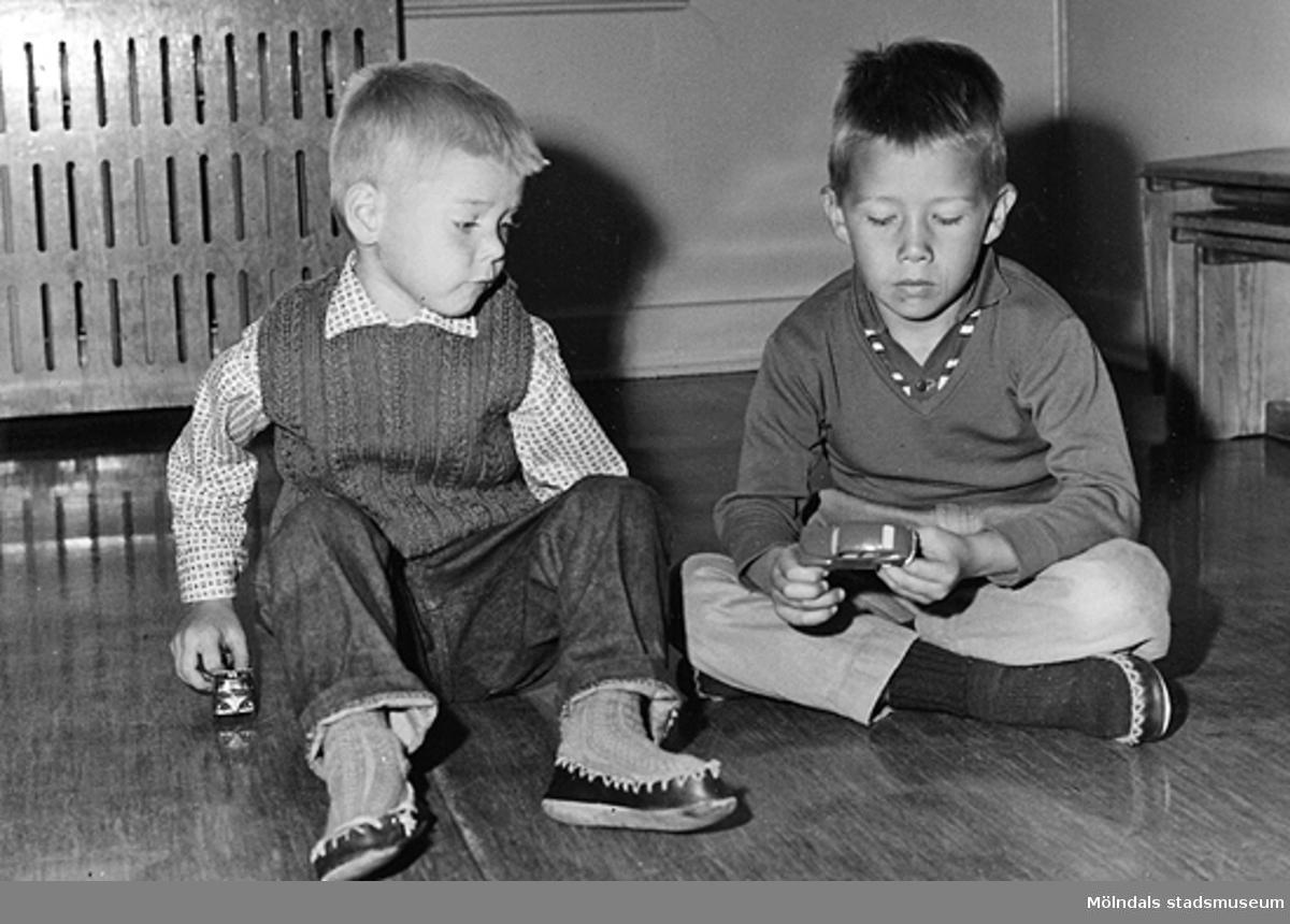 Två pojkar som sitter och leker med bilar. Holtermanska daghemmet 1953.