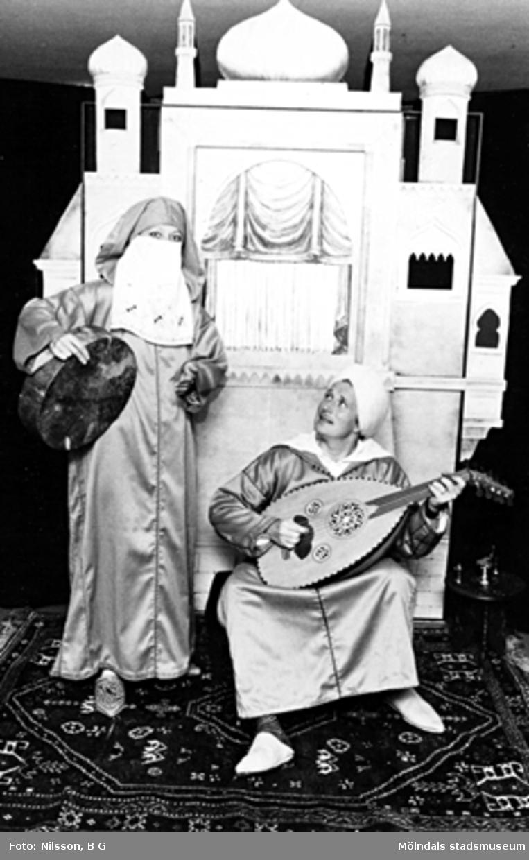 Två vuxna personer utklädda i orientaliska kläder, båda hållandes var sitt instrument. I bakgrunden står ett orientaliskt palats i mini-format. Holtermanska daghemmet 1973.