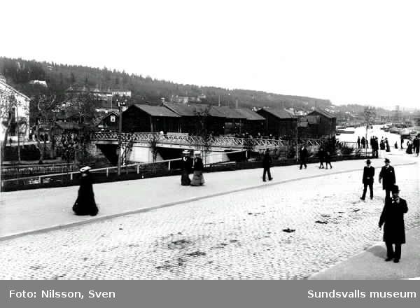 Flanörer efter västra delen av Storgatan. Storbron och magasinen på Norrmalm i bakgrunden.