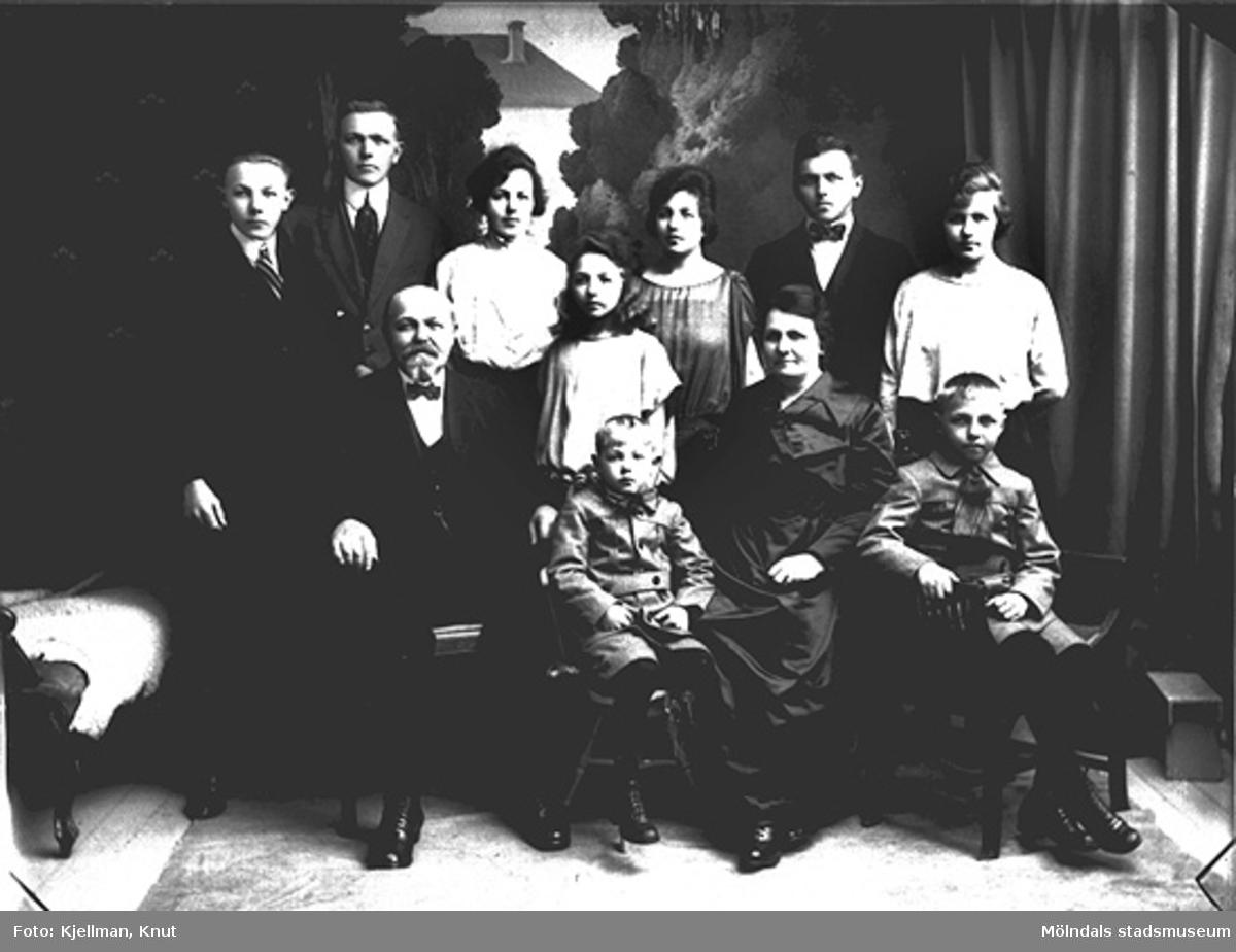 På baksidan finns en lapp påklistrad med texten: Mölndal, Glas, år 1915. Fotot föreställer August Persson, åkeriägare i Gårda (Göteborg), med familj.