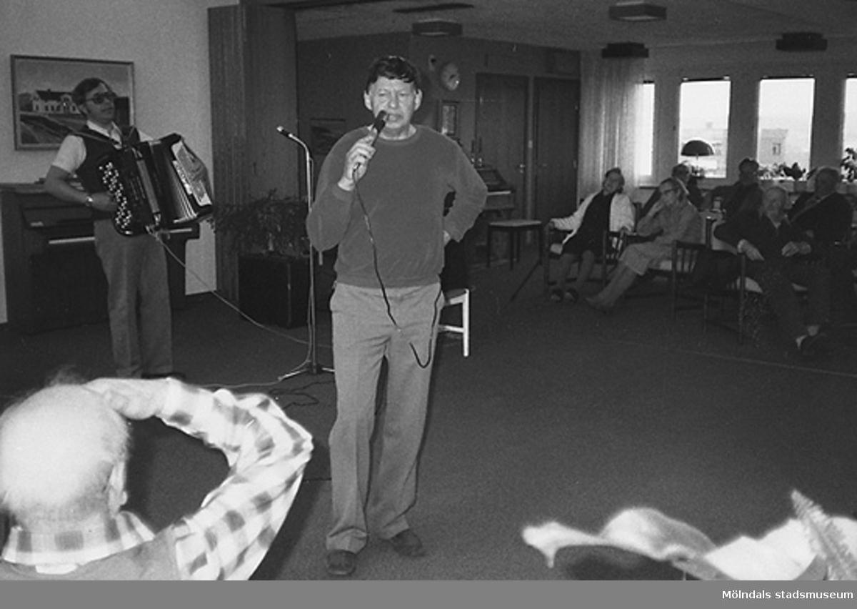 En man spelar dragspel och en annan man håller en mikrofon. Det är underhållning och de boende sitter runt omkring. Okänt årtal.