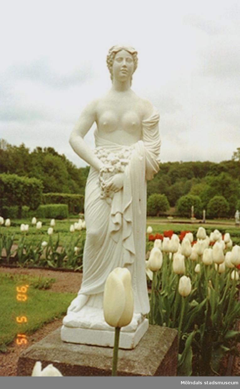 """Marmorskulptur """"Våren"""" av Gioacchino Frulli (1766-1801) placerad vid blomsterrabatter med tulpaner i."""