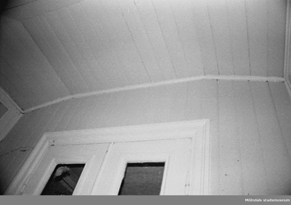 Interiör i fabriksbyggnad. Byggnadsdetaljer: En halv dörr och taklist.