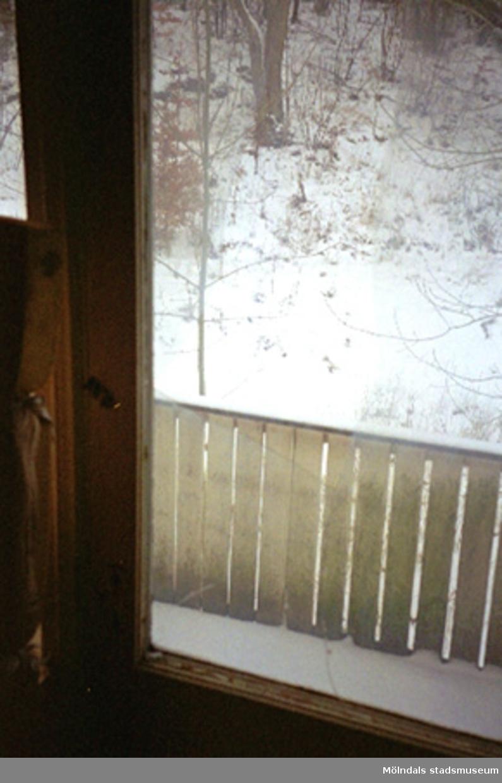 Ett trasigt fönster. Utanför fönstret finns en veranda med ett staket.