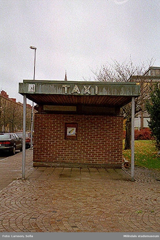 Vy åt väst på tegelbyggnadens kortsida med TAXI på takblecket. Tempelgatans byggnader ses till vänster samt två parkerade bilar. Dokumentation av taxistation.