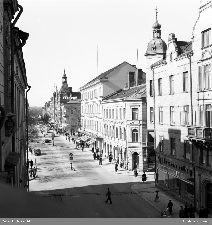 Vy över Storgatan taget från hotell Knausts balkong. Folkvimmel och butiker som Heselius, Ålunds kläder, med flera.