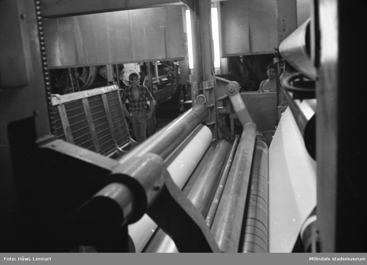 Män i arbete vid rullmaskin 5, byggnad 10. Rullmaskinförare Göran Sjöberg, t.v. Papyrus i Mölndal, hösten 1970.
