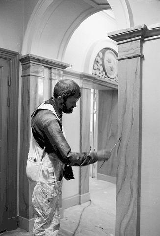 Marmoreringsarbete i den inre delen av Postmuseums entréhall. Snett bakom målaren finns hissen.