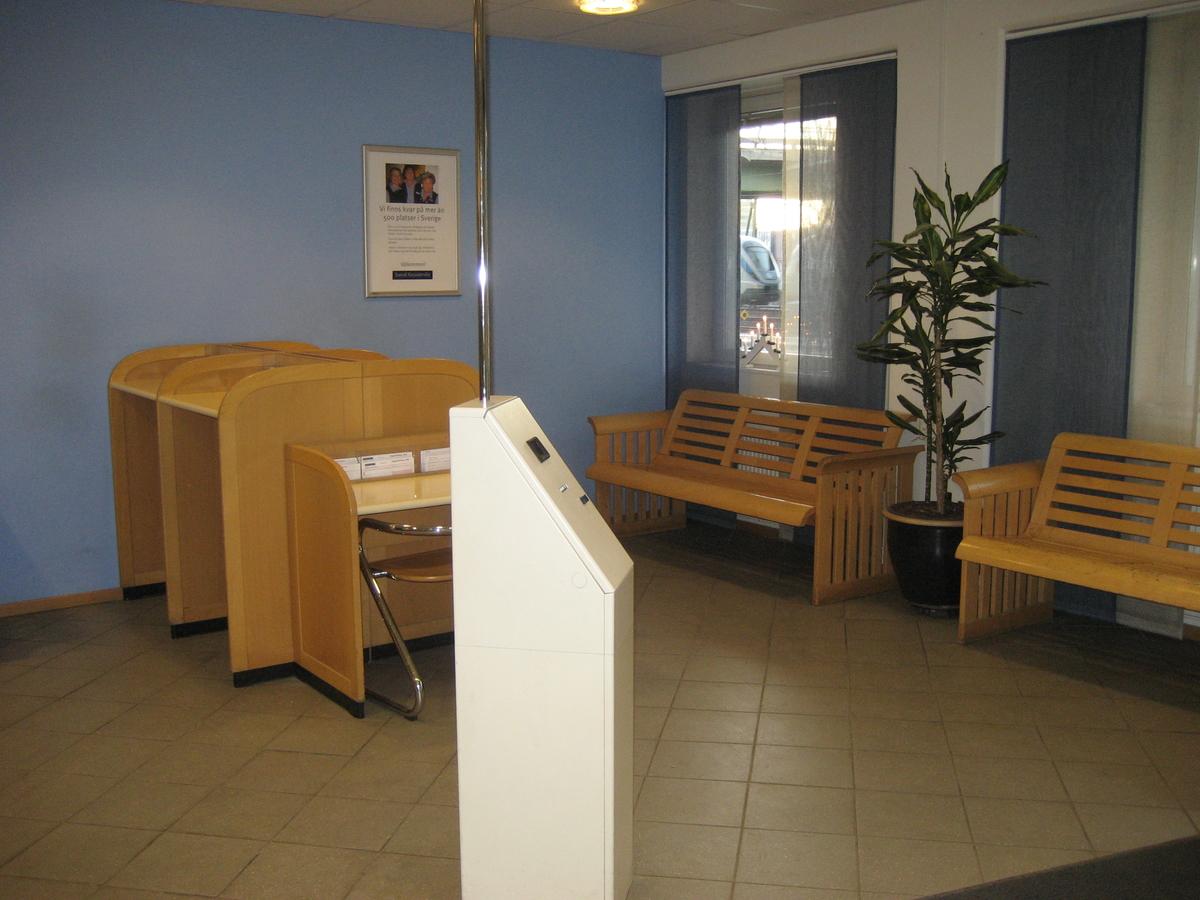 Allmänhetens sal med kölapps automat i förgrunden. I bakgrunden ståpulpeter och en plats för sittande. Bänkar att vänta på vid fönsteret.
