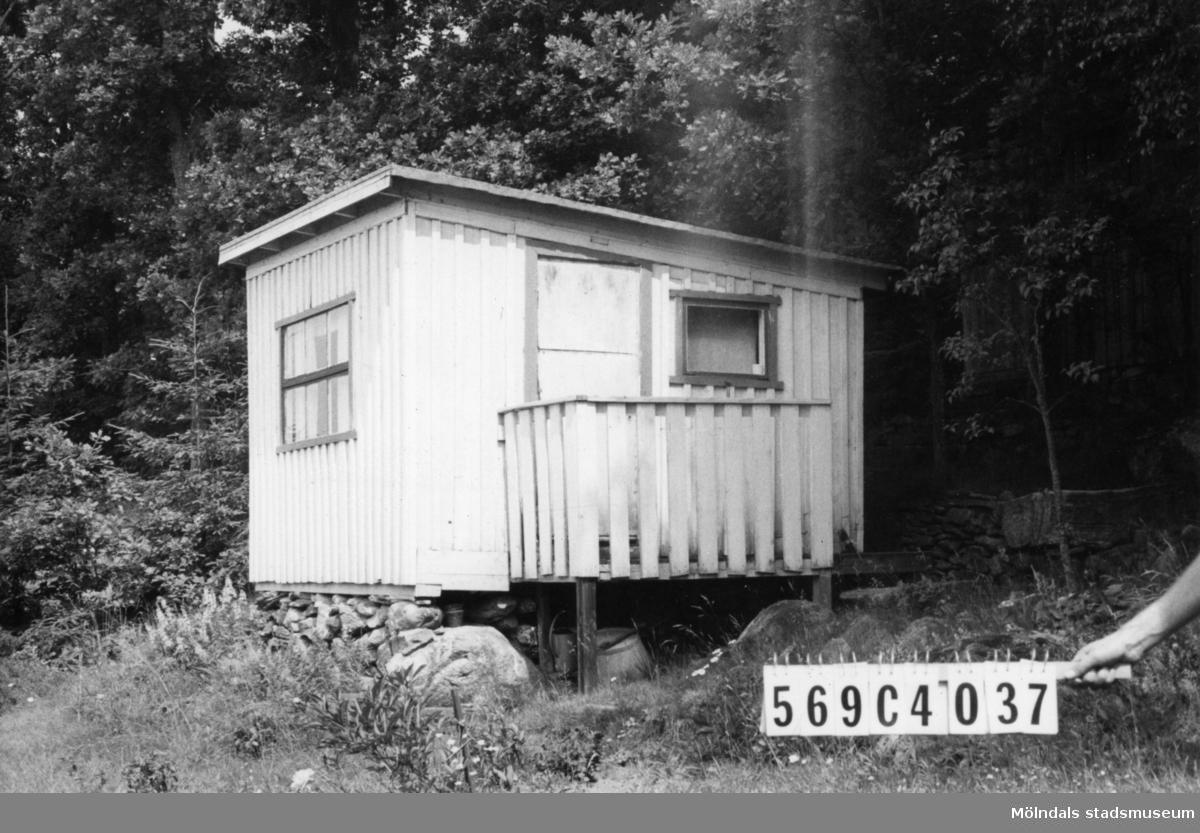 Byggnadsinventering i Lindome 1968. Gårda 2:64. Hus nr: 569C4037. Benämning: fritidshus och redskapsbod. Kvalitet, fritidshus: dålig. Kvalitet, redskapsbod: mindre god. Material: trä. Övrigt: verkar dåligt skött. Tillfartsväg: framkomlig. Renhållning: soptömning.
