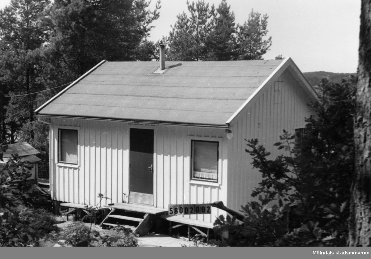 Byggnadsinventering i Lindome 1968. Hassungared 3:24. Hus nr: 580D2002. Benämning: fritidshus och redskapsbod. Kvalitet: god. Material: trä. Övrigt: redskapsbod byggs till. Stökigt, ej färdigt. Tillfartsväg: framkomlig.