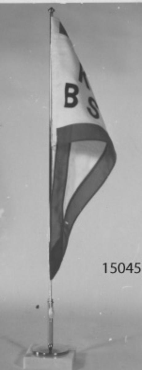 Vit med 35 mm röd bård. I inre delen av det vita fältet texten KBS (Karlskrona Blekingseke Sällskap) i svarta bokstäver. Flaggstången av metall med fot av marmor.
