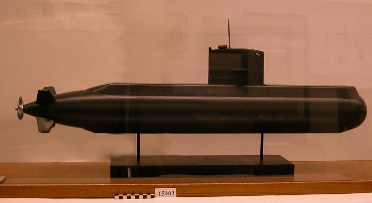 Ubåtsmodell av Näcken. Gjuten i plast grafitgrå. Skala 1:50. Gjuten fartygsmodell i plast, modellen är målad i grafitgrå färg, vilket även är originalfärg på denna typ av ubåtar. På varja sida av tornets främre del målat i vitt Näk vilket är förkortningen på fartygets namn, Näcken. Den fembladiga propellern är målad i bronsfärg.