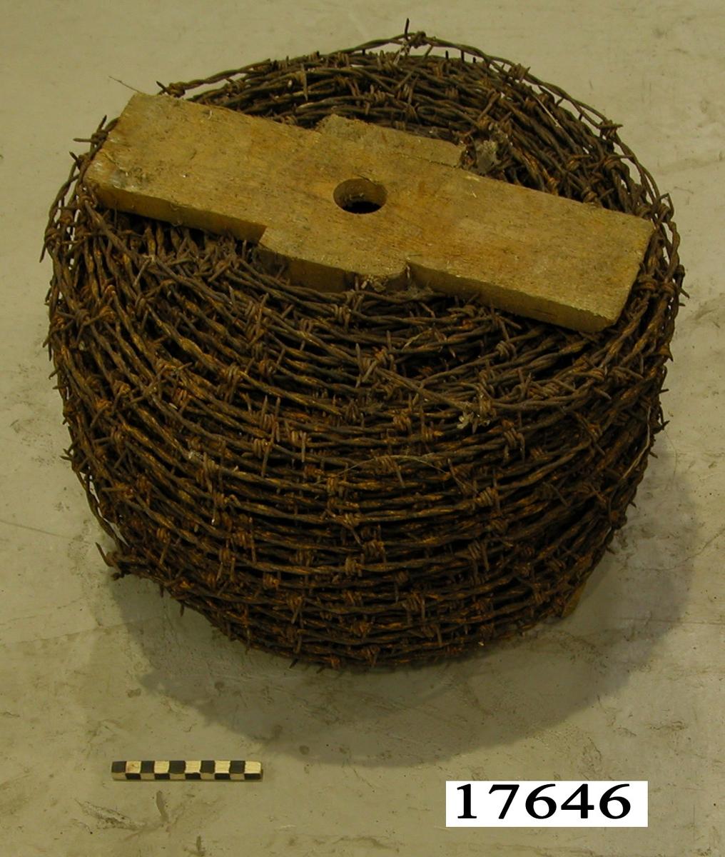 Taggtråd upprullad på trätrissa vars tvärslåar är försedda med hål, så att trissan kan sättas på en pinne. Över 20 meter taggtråd.