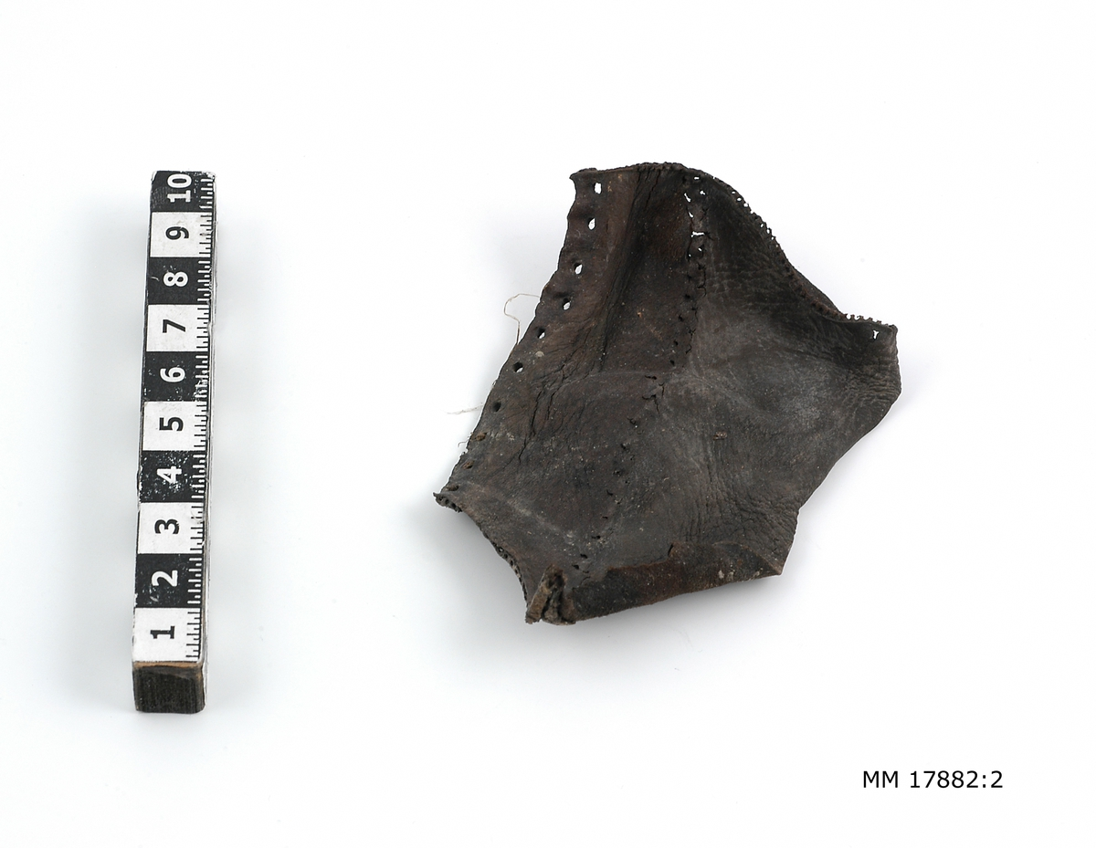 Sjöfynd från vraket Nya Riga. 16 fragment av läder, flertalet tydliga rester av skor med sula och klack försedd med pliggar. Spår efter sömmar. Hälften är större fragment.  För dimensioner på de enskilda bitarna, se inventariebilaga.