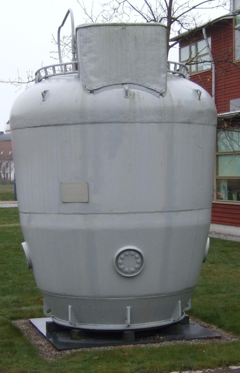 Räddningsklockan Göta av järn, gråmålad, oval form. Nedgångslucka på ovansidan med räcke. Öglor i kanterna och ventiler.