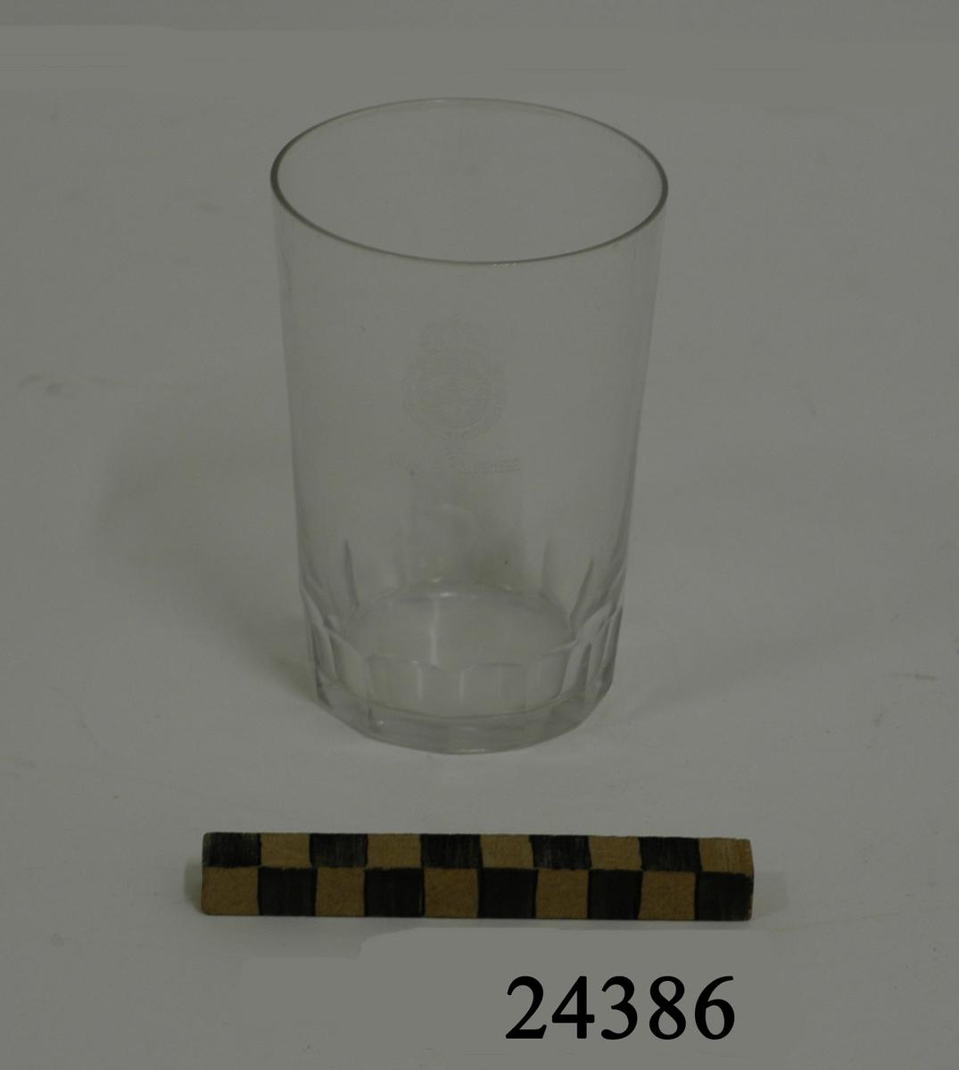 """Dricksglas, rakt cylinderformat, utan fot. Bågformad slipning i glasets nedre kant. På glasets mitt slipad dekor: lilla riksvapnet omgivet av koldinerorden därunder: """" H.M.S SVERIGE """""""