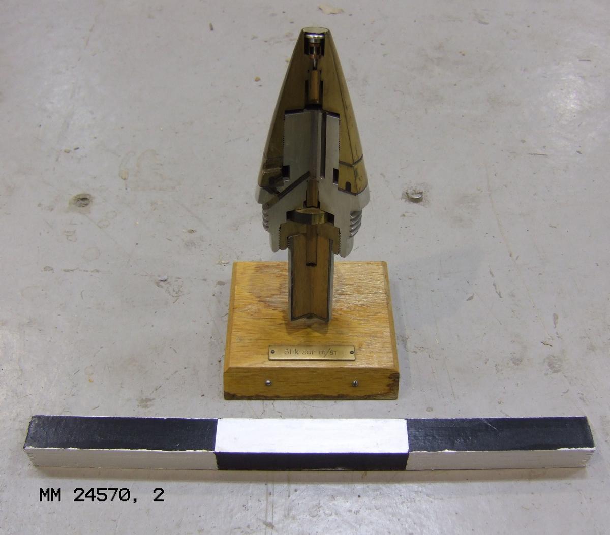 """Demonstrationsexemplar av sjömålsgranat fästad vid stativ av trä. Metallplatta ovanpå trästativ märkt """"öhk sar m/51"""". Märkt undertill """"O. Nyberg VaB 2 / A""""."""