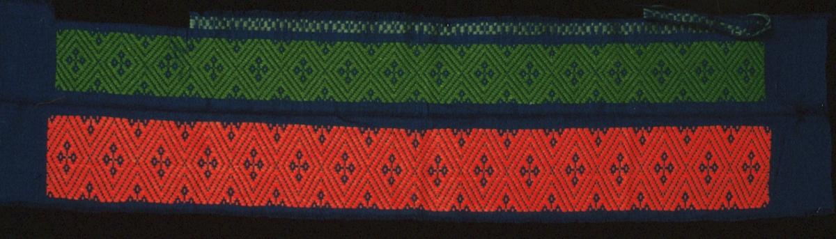 Vävprov i opphämta. Korsblomma i rombmönster. Blå botten med en rödorange bård och en grön bård samt en smal blågrön bård i avvikande färg, garn och mönster. Varp i blått 2-trådigt s-tvinnat bomullsgarn, 20 trådar/cm.Botteninslag samma som varpgarnet, 17 trådar/cm.Mönsterinslag i 2-trådigt s-tvinnat ullgarn. En liten bit är bortklippt men påtråcklad igen.