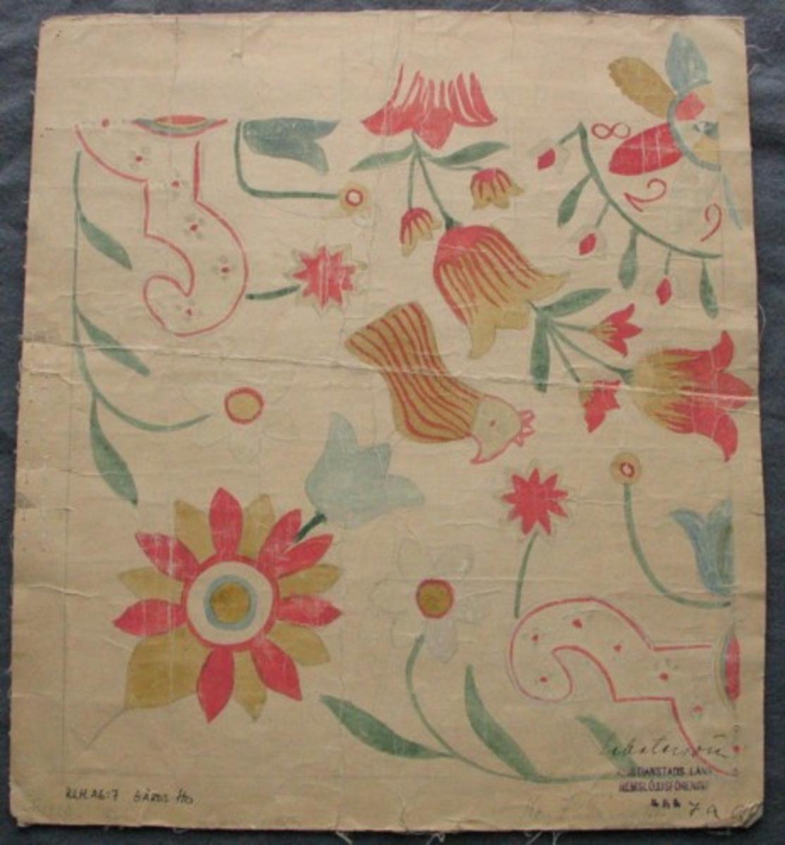 """Skiss avritad på tygförstärkt papper. 1/4 av kudde. I mitten en åttabladig blomma. Runt blomman en liten krans med utåtgående blommor och blad. Runt detta en tulpankrans. I hörnet en flikig blomma, från denna en tulpan med stående fågel. Mellan hörnen beslagsliknande ornament. I mitten en utväxande tulpan och vid sidorna anemoner. Mellan bladen på mittblomman är årtalet 1829 broderat. Gammal märkning: """"Nr 7, Gärds Hd, Pl 1220. 60x60 cm, svart botten. Schatersöm""""."""