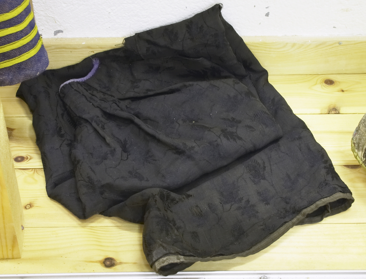 Forkle i svart ulldamask. Linning i fiolett moherband 18 x 0,6 cm. Follelagt i livet. Rundkanting ned 1 cm bred med et tynt ullband.