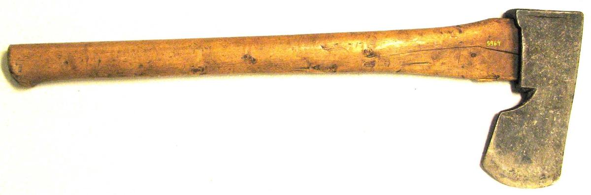 """1 """"huggeøks""""  (boløks)  Ligner noget den sognske smalkjæftaøks, men er bredere, samt boløksen fra Raabyggjelaget. Den er formentlig den oprindelige boløks i Valdres. Har utpræget kverke og paasveiset """"nakkeskjel"""" (Konf. no. 5199). Fremsiden danner en ret linje. Paa bladet anbragt smedemærket TOS. Bredde ved eggen 9,5 cm, øksens længde 20,2 cm, skaftets længde 62 cm. Kjøpt av lensm. Eivind Berg, Østre Slidre, Valdres."""