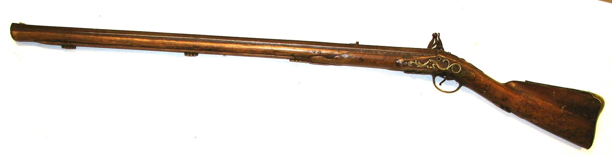 Form: Åttekanta løp. 1 gevær.  Helskjæftet rifle med flintelaas. Löpet, der er ottekantet har svært kaliber og har indvendig 9 rifler. Löpets længde 90,2 cm. Laaset er mærket M. Stones. Kolben og skjæftet har vakkert messingbeslag. Har tilhört fam. Holck, Alværa.  Gave fra enkefru Hartwig, datter av eidsvoldsmanden generalmajor Holck, Alværen gaard i Lavik. Efter hendes bestemmelse blev disse gjenstande efter hendes död des. 1914 av executor testamenti hendes nevö, dr. Chr. Hartwig, Bergen, skjenket museet.