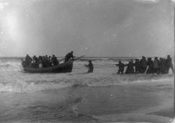Livbåt full av folk dras i iland på strand.