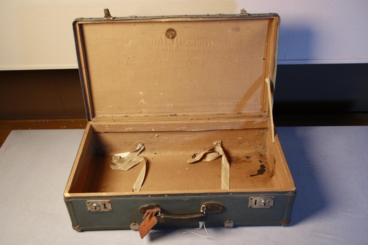 Koffert i vulkanfiber. Forsterka over hjørner og sider med metallplater. Handtak og to låsar. Sett saman med naglar. Inni er kofferten trekt med mønstrete papir. Festestropper i stoff.