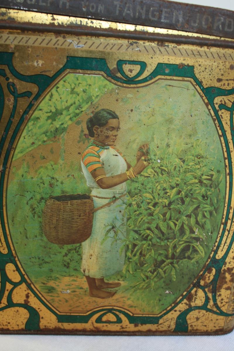 Metallboks brukt til te med dobbelt lokk. Begge lokk firkanta og hengsla. Ytre lokk har hatt motiv, men øydelagt av rust. Motiv frå teproduksjon. Fire ulike motiv, eit på kvar side. Første: Ei kvinne plukkar teblader. Andre: Teplukkarar på veg tilbake med korger fulle av blad. Tredje: Ein te-plantasje. Fjerde: Arbeidarar med tekasser bore på hovudet. Lesbar påskrift på kassene Finest Ceylon Tea, Adolph von Tangen Jordan Bergen.