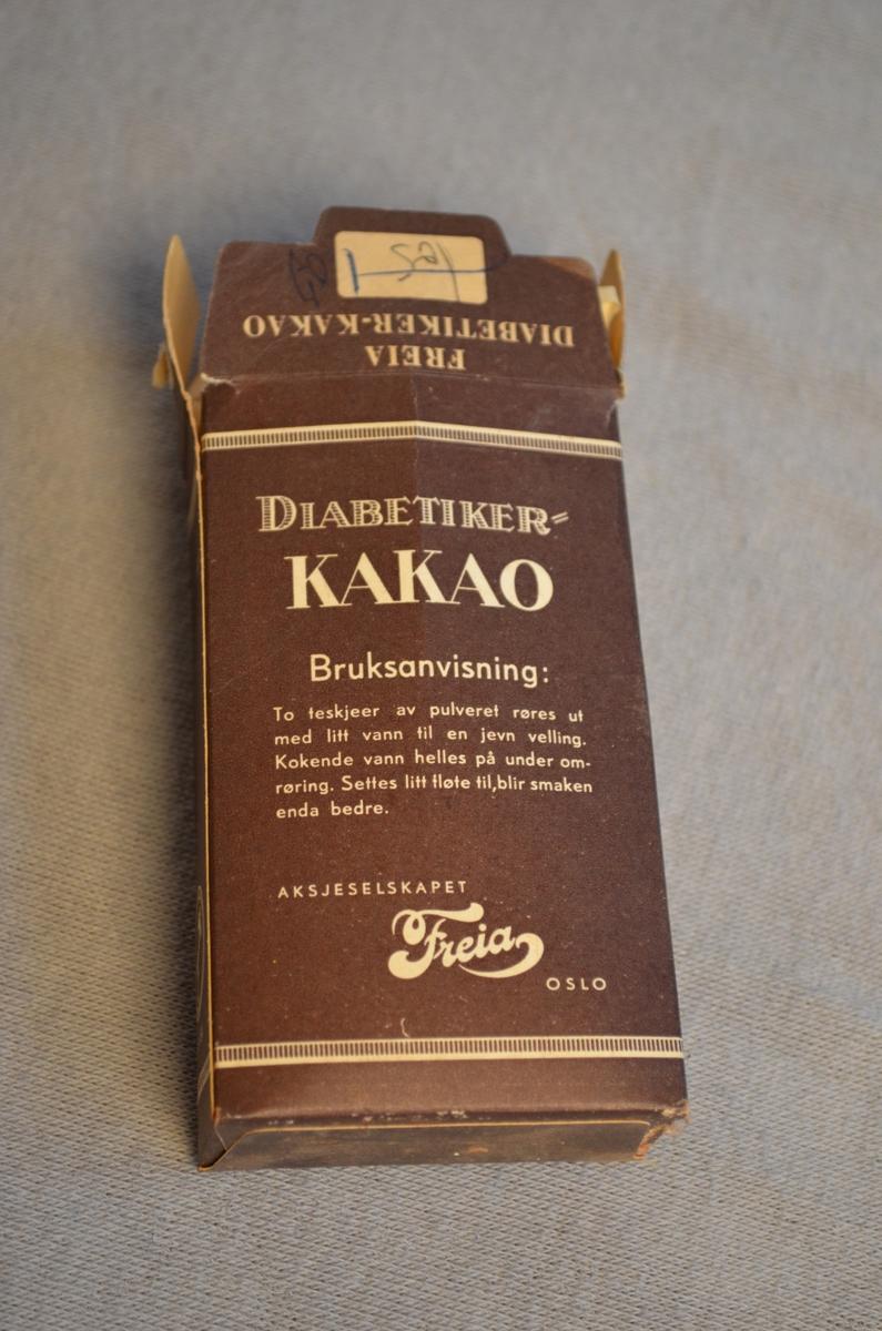 Pappeske med diabetiker-kakao frå Freia. Den er framleis nesten full. Pakken er brun med kvit skrift.