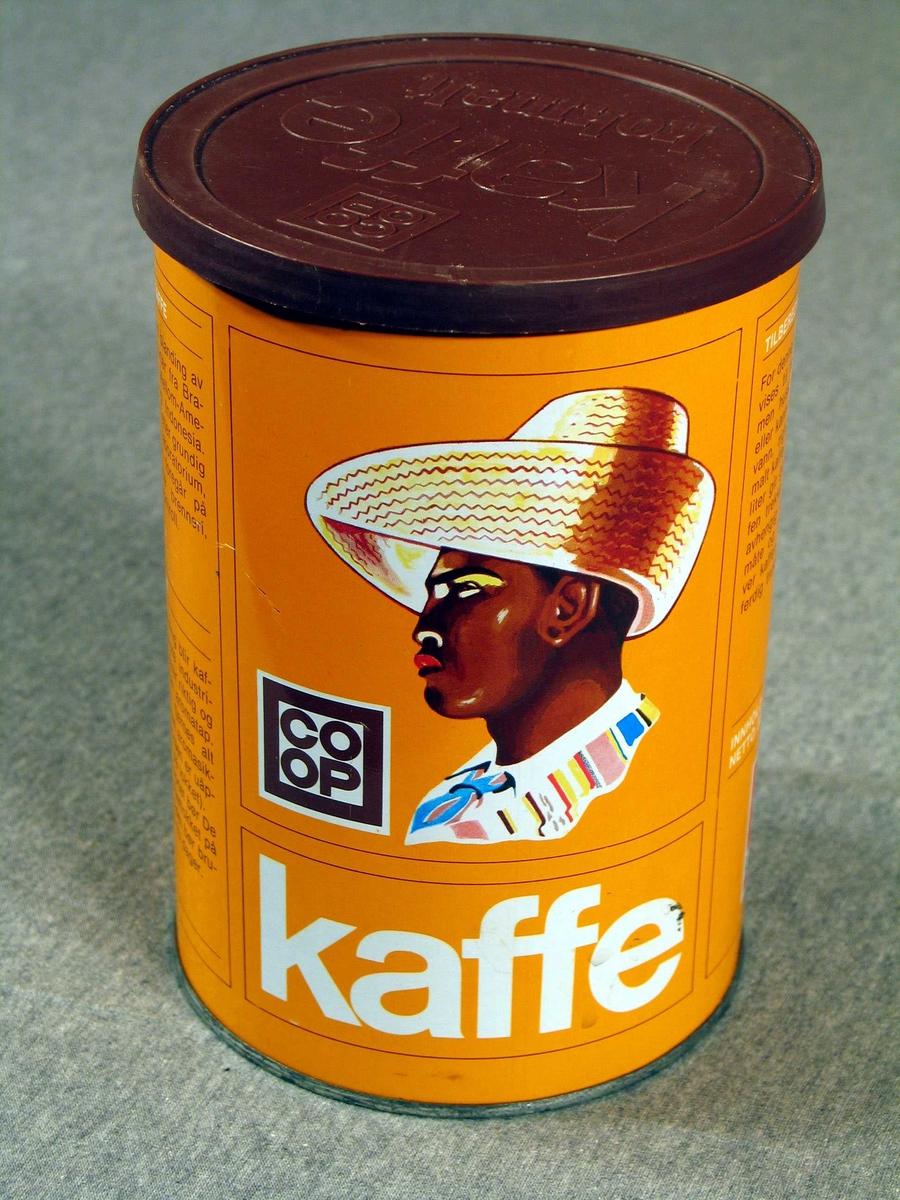 """Malt portrett av svart mann med sombrero (kaffiplantasjearbeidar), Co-op sin logo og """"kaffe"""" med stor skrift på to """"sider"""" av boksen. På den eine er også skrive """"Aromasikret"""" i eit skrått felt over sombreroen. Elles tekst under overskriftene GUL CO-OP KAFFE, AROMASIKRET og TILBEREDNING"""