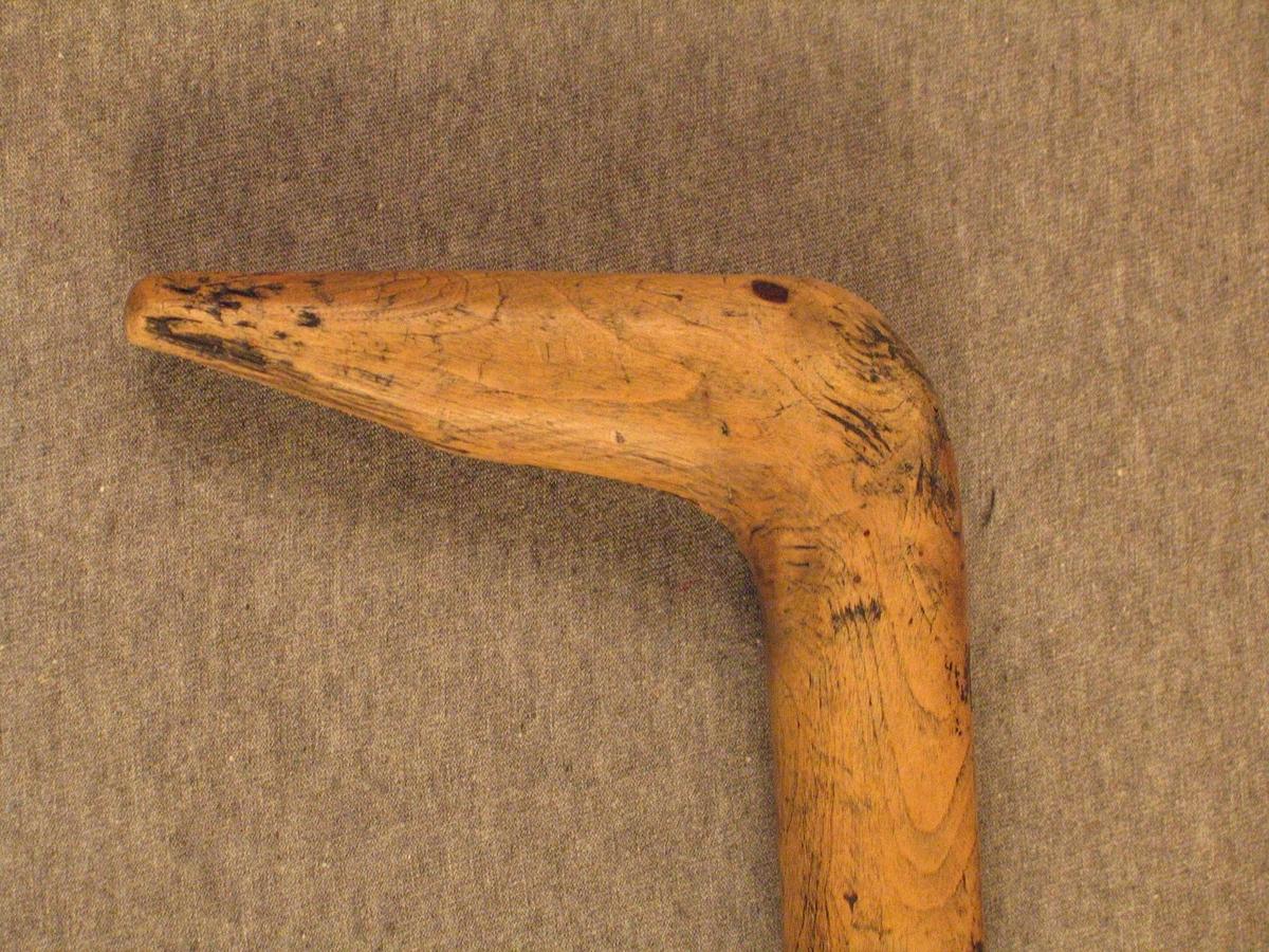 Stokk med naturvaksen krok. Stokken har vore måla svart, men mykje av målinga er borte. nederst er det sett på ein skoning av slaneggummi. det ser ut som at stokken har hatt pigg.