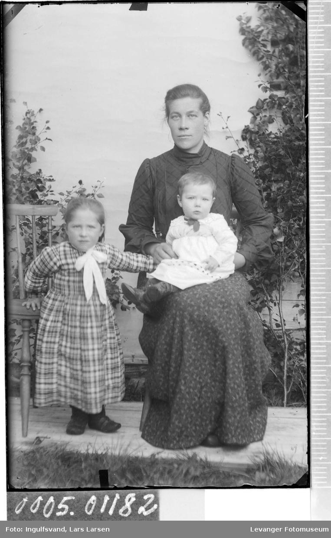 Portrett av en kvinne og to barn i helfigur.