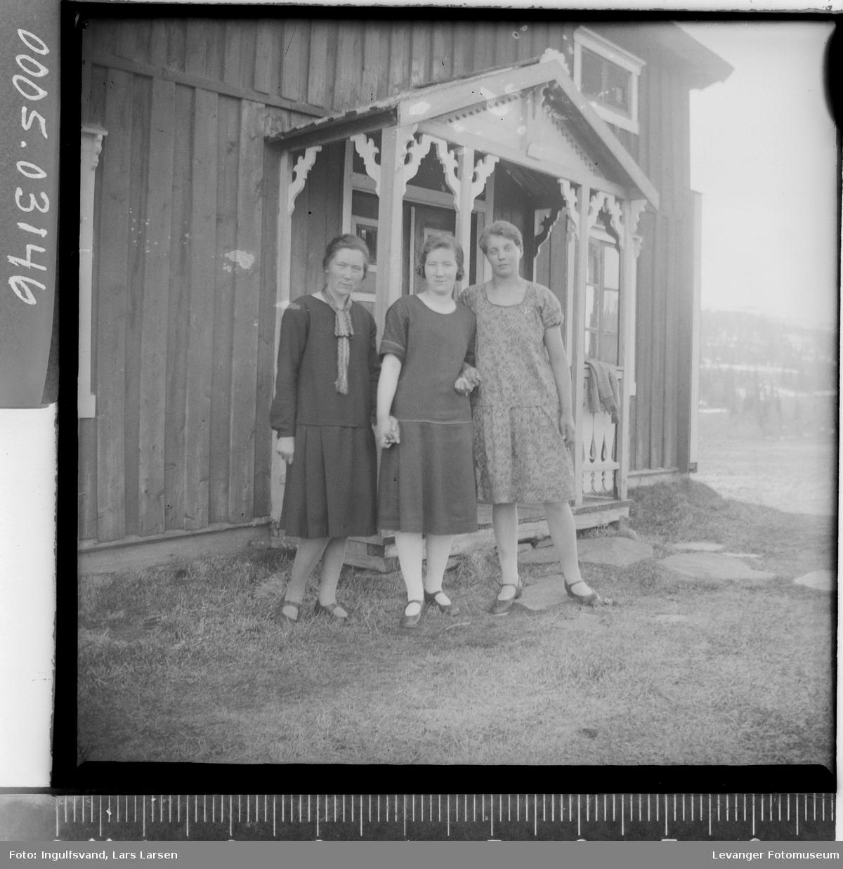 Gruppebilde av tre kvinner ved en bygning.