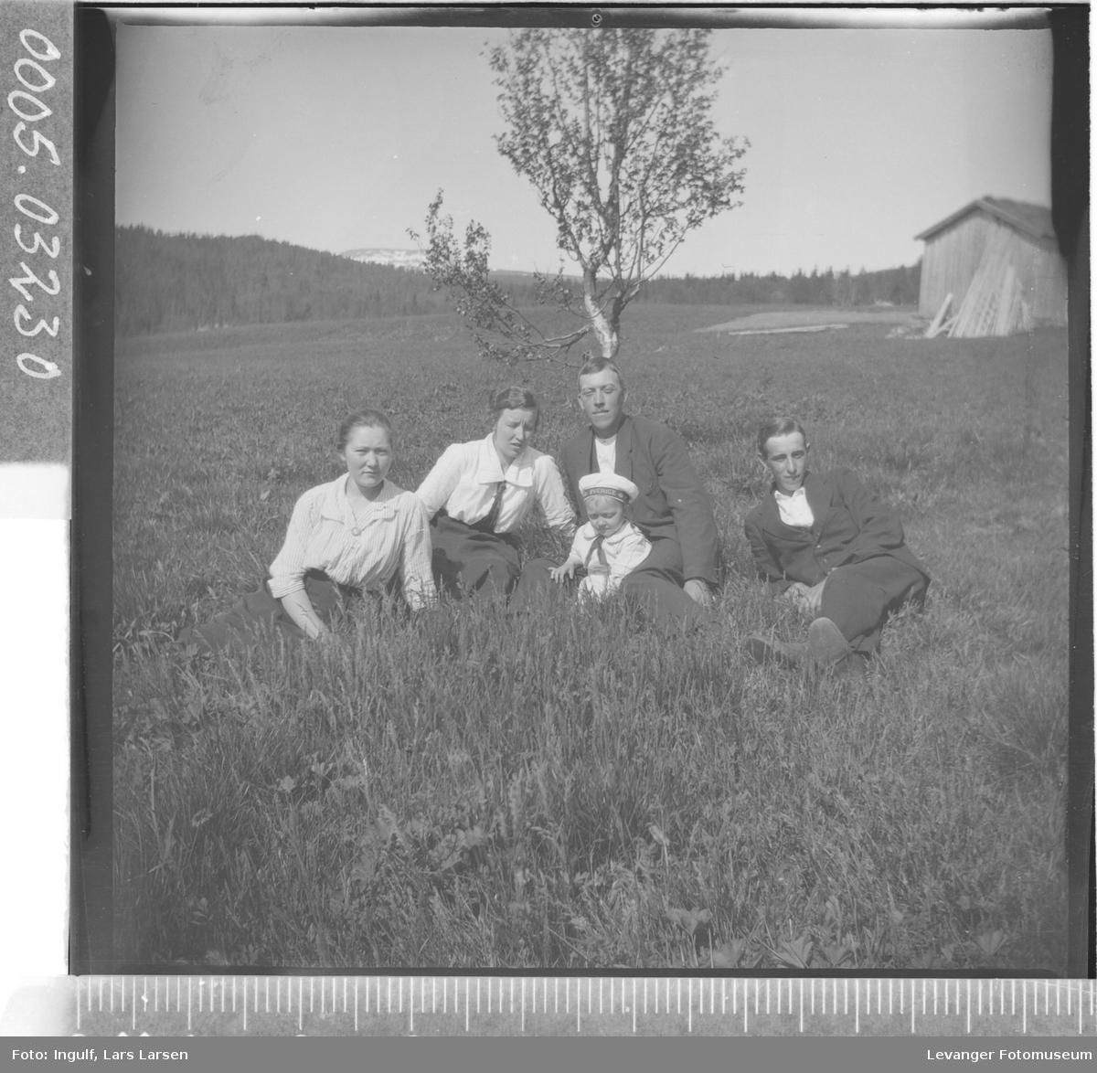 Gruppebilde av to kvinner, to menn og en gutt som sitter i gresset.
