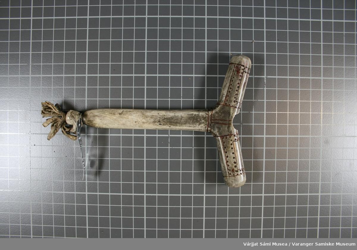 Moderne replika av hammer til runebomme / sjamantromme. Hammeren er laget av horn. Den er grå og har noen skinnbiter som henger nederst. .
