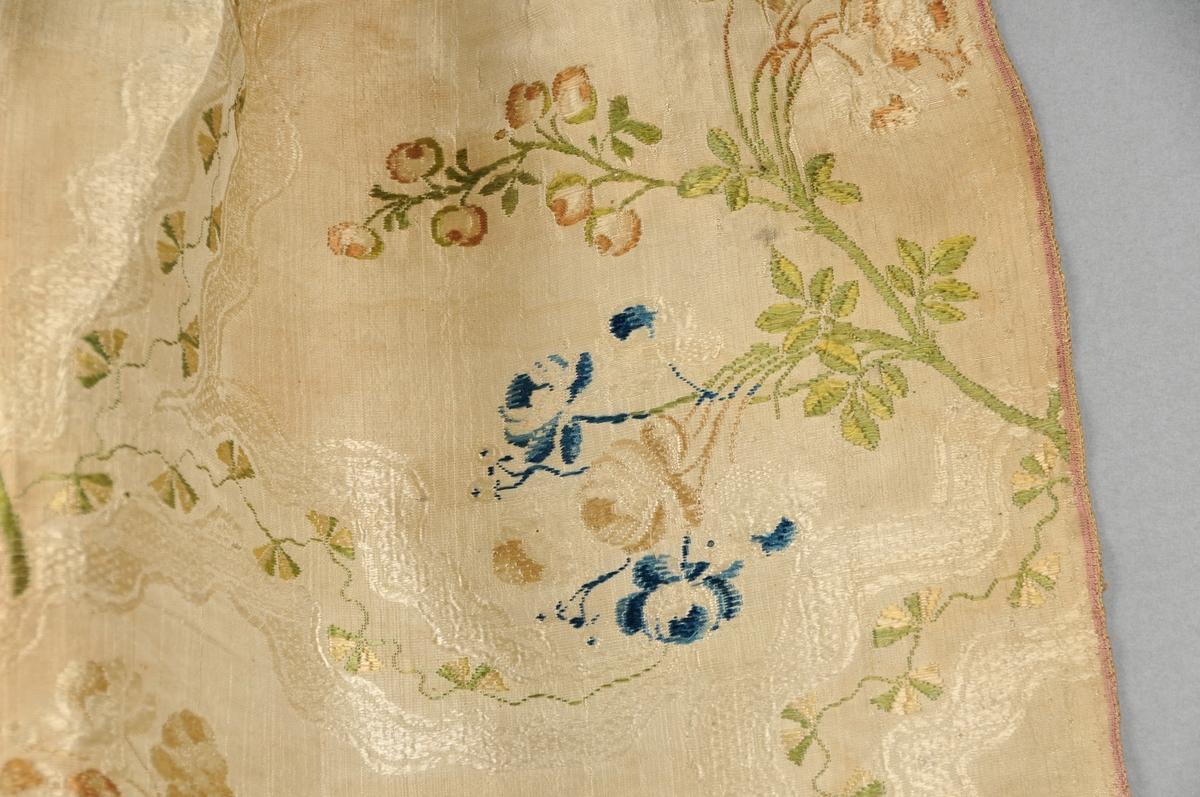 Forkle i brosjert silkedamask. Beige botnfarge og med blomstermønster i grønt, brun-rosa og blått.  Samansett av to høgder (stoffbredder, jarekant på begge sider).  Påsett linning i bomullslerret. Fem legg på kvar side, lagt mot midten. Falda dobbelt nede.