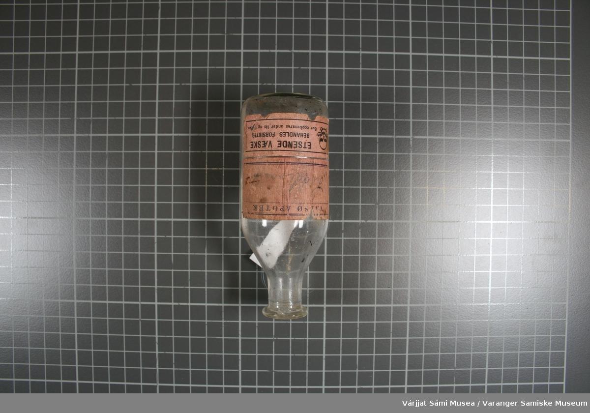 Loddebolt med håndtak av tre. Den er sotat. Bolten er av messing.                                                                     Liten flaske. Flaska har inneholdt loddevann. Flaska av blankt glass. To etiketter limt  på flaska. På den øverste etiketten står det. VADSØ APOTEK. Skrevet med blyant loddevann. På den nederste etiketten (den har løsnet noe) står det: ETSENDE VÆSKE                                                                                     BEHANDLES FORSIKTIG                                                                 BØR OPPBEVARES UNDER LÅS OG LUKKE  Korken til flaska ligger nedi bunnen. I bunnen står ett 3 tall                                                                             100                                                                              644