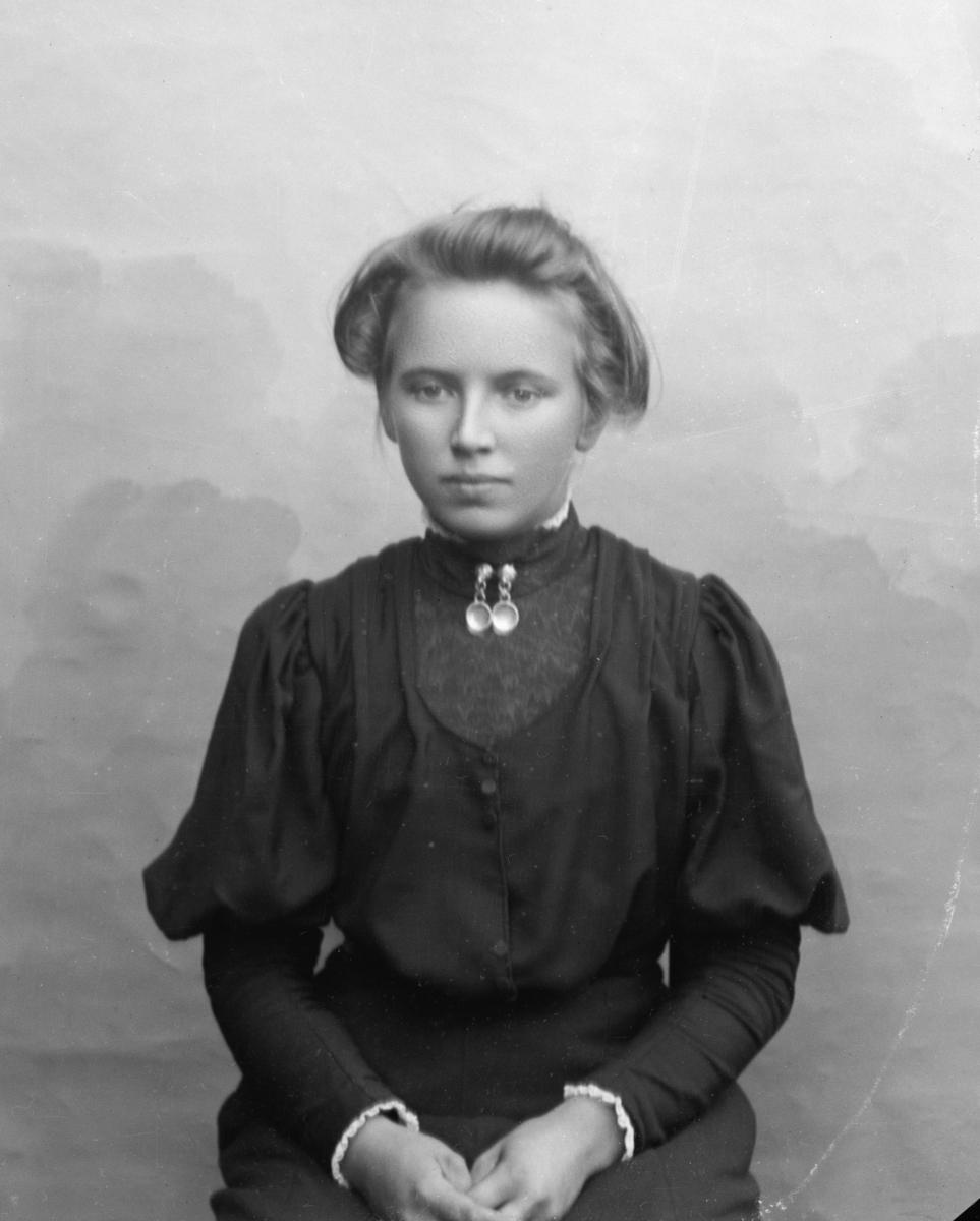 Ung kvinne sittende foran lerret