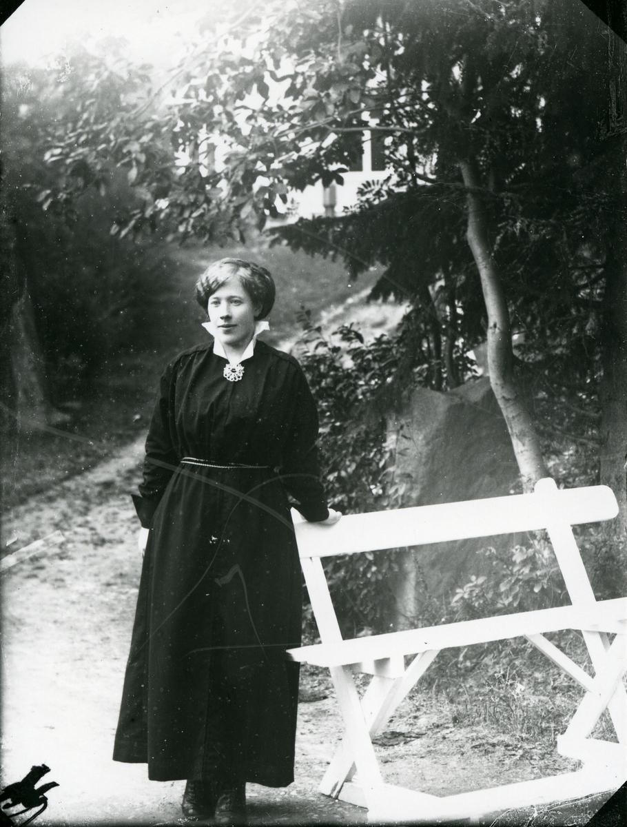 Kvinne ved hvit benk, fotografert på vei med skog og hvit bygning i bakgrunnen