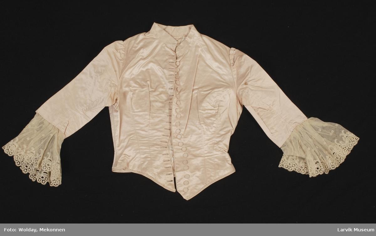 Form: Innsvingt jakke med spiler. kinakrage. Stofftrekte knapper i front, 3/4 lange ermer, blonde nederst på erme. Jakken former en spiss foran og bak.