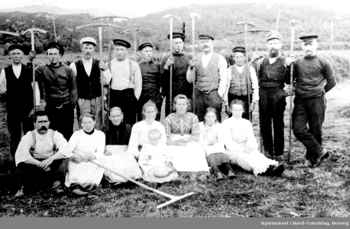 """Rørvik-engan"", rakedugnad. Foran fra venstre: Albert Engstad, Janna Lysø, Seriana Haug, Petra Formo Haltvik med Snefryd Formo, Lydia Haug, Vanda Ulsund, ukjent og Amanda Reiersen. Bak fra venstre: Los Ole Haug, Paul Haug, Edvin Haltvik, ukjent, Reginus Skulestad, Sigurd Haug, Ulrik Engstad og Håkon Reiersen."