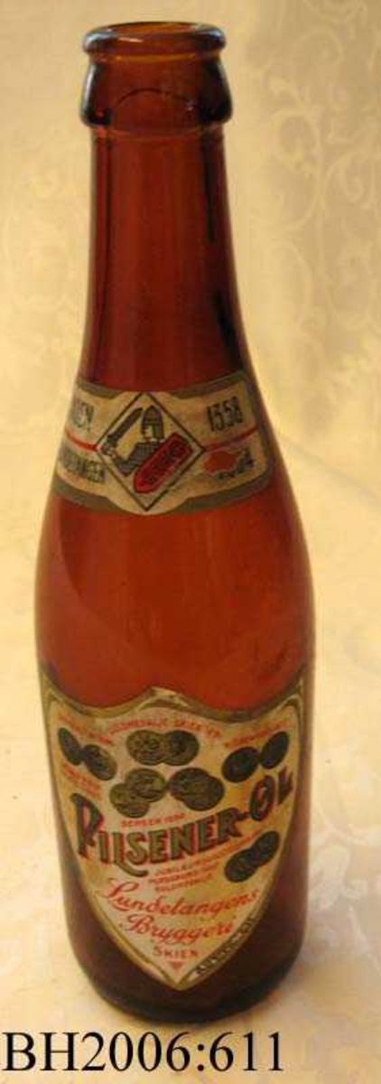 Ølflaske av brunt glass med  etikett av papir på flaskens front.