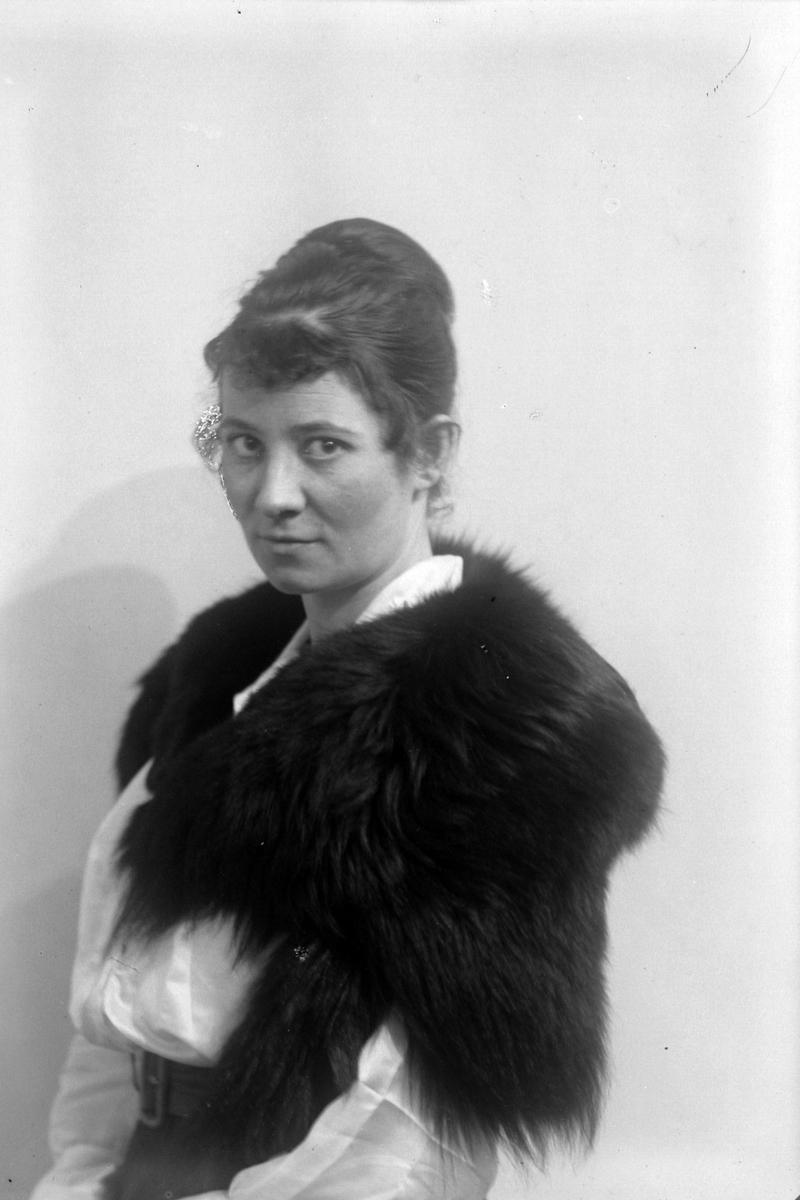 Studioportrett av en pelskledd kvinne i halvfigur.