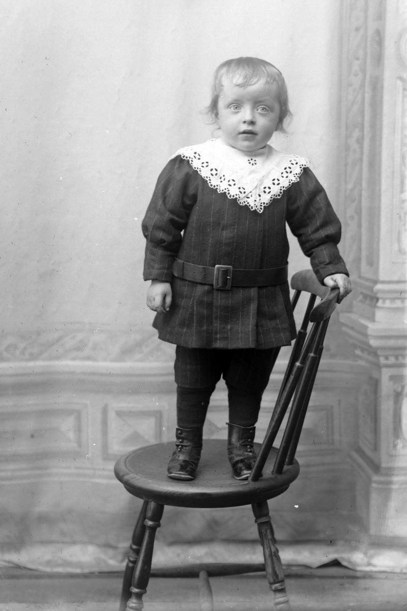 Studioportrett i helfigur av et barn stående på en stol.